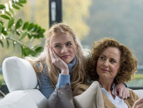 A teenage girl and a middle-aged woman sit on a couch. The teenage girl has her head on her chin while the woman looks at her in a way that suggests she is frustrated.