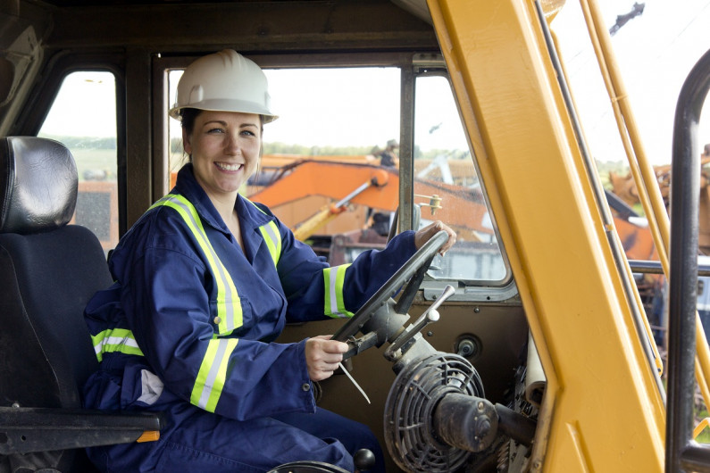 Female construction worker sits in a digger and smiles at the camera.