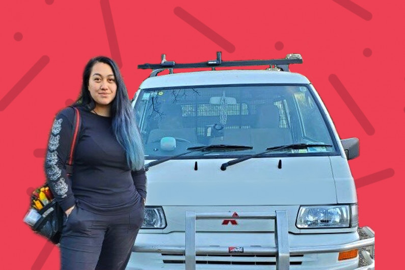 Cori Potaka, electrical engineering technician stands in front of her work van
