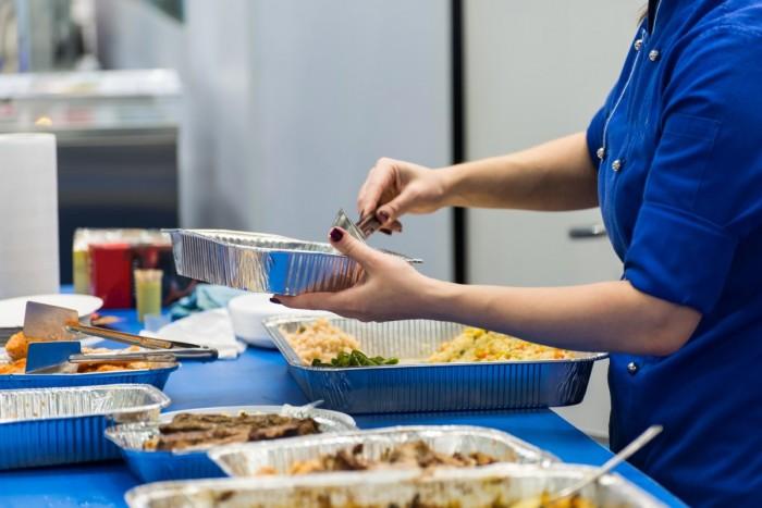A cook preparing to serve food