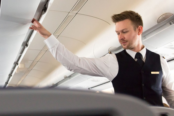 A flight attendant secures an overhead storage container
