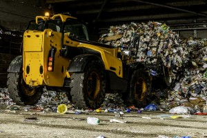 A bulldozer compacts plastic in a recycling plant