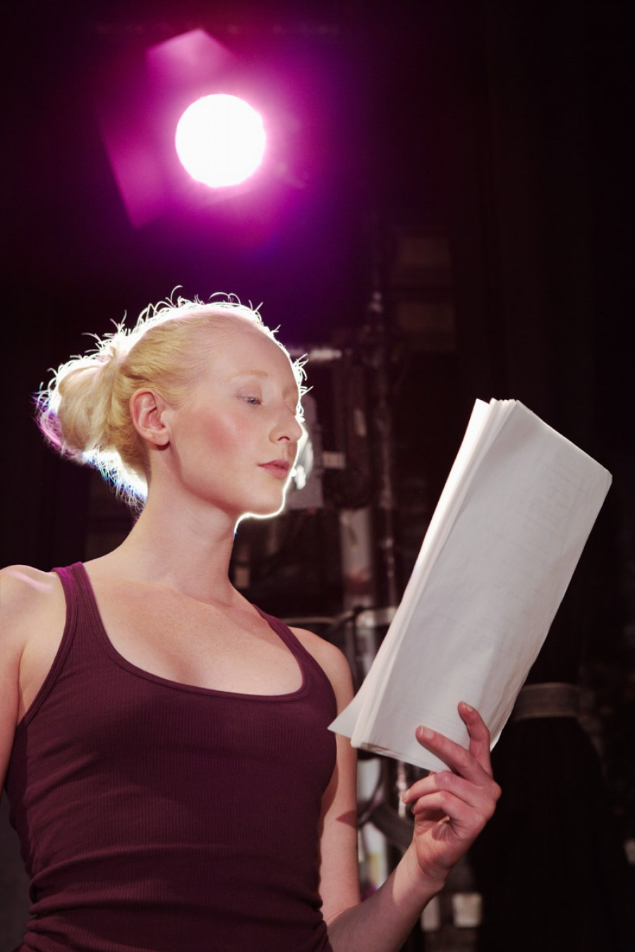 A student reads a production script on stage